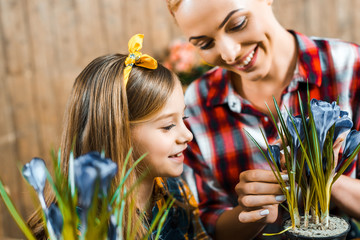 happy mother touching flowers in pot near cute daughter