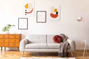 Stylish vintage decor in a spacious flat interior with design grey sofa, armchair, retro commode and posters on the wall. Brwon wooden parquet, stylish carpet and plants. Bright  living room.