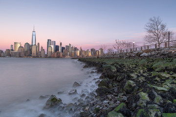 Financial district view from jersey city coastline at sunset with long exposure