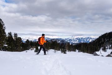 Man snowshoeing on Scheibelalm in Hohentauern view to Ennstaler Alps