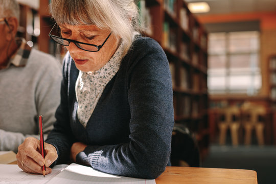Close up of a senior woman writing in her book