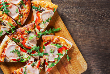 Pizza with Mozzarella cheese, mushrooms, ham, tomato sauce, pepper, Spices and Fresh arugula. Italian pizza on wooden table background