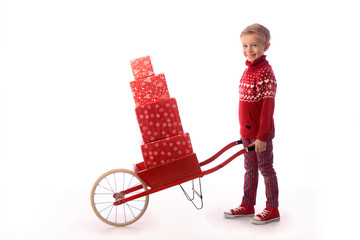 A boy, a child in a red sweater and a Santa's hat carries presents. Santa's helper. A nice child to advertise Christmas products. White background. Isolated.