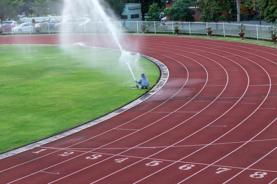 System working on fresh green grass on football or soccer stadium. Sprinkler watering field football. Automatic water irrigation in action. Close-up sprinkler of automatic watering.