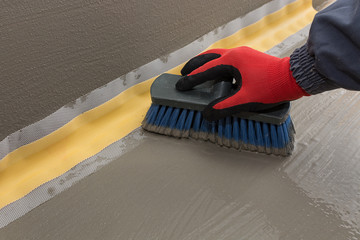applying the waterproofing layer over sealing tape, waterproofing tape