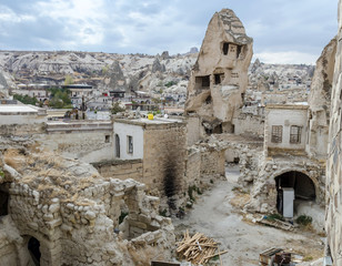 The horizontal view of collapsing rock pillar with dovecote cave inside and abandoned house yard, damaged walls in Goreme city of Cappadocia region, Turkey
