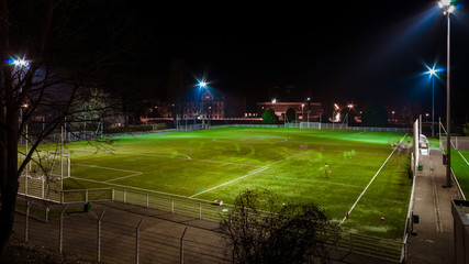 Green football field highlighted at night with trces of people running