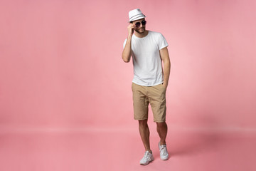 Full length of attractive confident young man in hat standing with hands in pockets over pink background. Wall mural