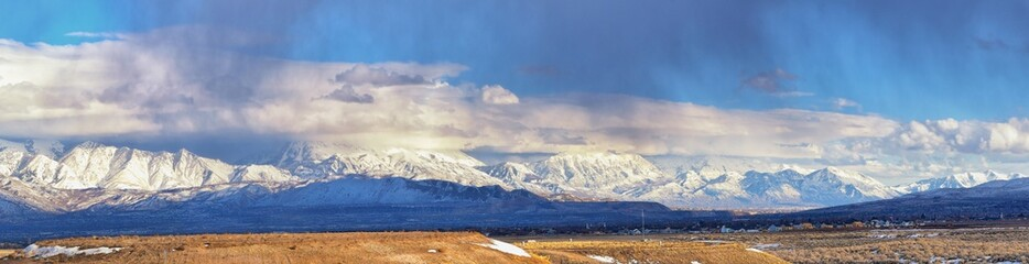 Winter Panoramic view of Snow capped Wasatch Front Rocky Mountains, Great Salt Lake Valley and Cloudscape from the Bacchus Highway. Utah, USA. Wall mural