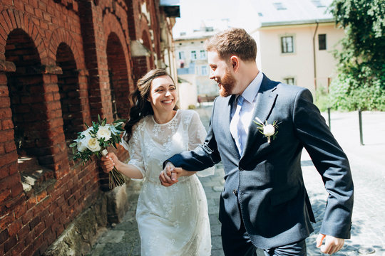 A beautiful wedding couple in the retro style sincerely have fun. Happy bride and groom have fun running together and looking at each other