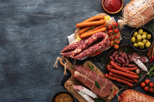 Assortment of Sausage and ham . Assorted meat products, including smoked sausages, ham and salami with vegetables and spices