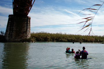 A family of migrants from Honduras cross the Rio Bravo towards the United States, in Piedras Negras