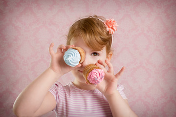 Funny little child girl with cupcakes on the vintage ornament background