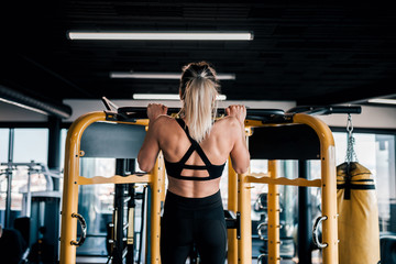 Young muscular woman doing pull up exercise in the gym.