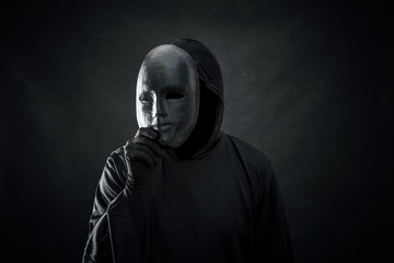 Scary figure in hooded cloak with mask in hand  Wall mural