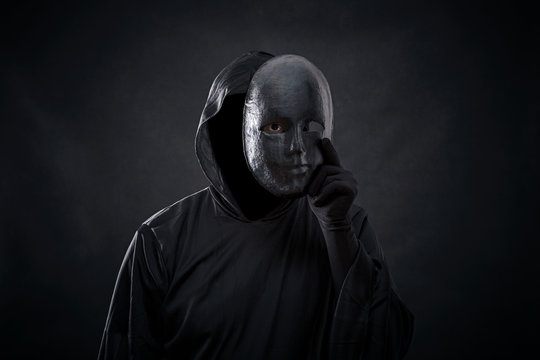 Scary figure in hooded cloak with mask in hand