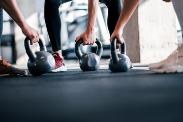 Lifting weights, low angle image. Athletes with kettle bells, close-up.