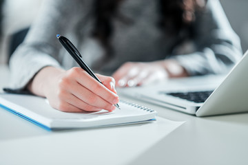Young woman executive working with laptop and taking notes.
