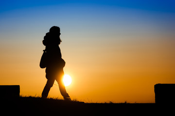 Silhouette of a young woman enjoying walking on the sunset