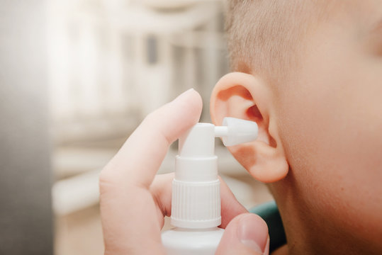 A parent cleaning the ears of a small child with a spray bottle. Hearing problems in children, clogged ears. The parent cleans the inside of the ear, errors when cleaning the ear .