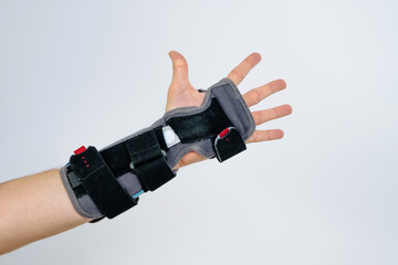 An orthosis placed on the hand on a white background. Protective orthosis stiffens the hand, joints during injury. Replacement of gypsum and splint with orthosis. Help with hand injuries. Hand pain.