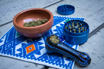 Marijuana in Blue Pipe with Grinder and Bowl of Cannabis