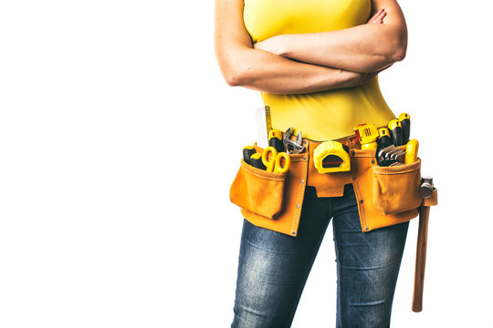 Handywoman with folded arms and tool belt isolated on white background.