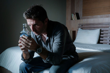 young depressed and wasted drunk man drinking vodka bottle at home sitting on bed thoughtful and confused as alcoholic suffering alcoholism problem and alcohol addiction