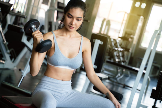 Youn sexy sport women exercise with dumbbell work out in the gym