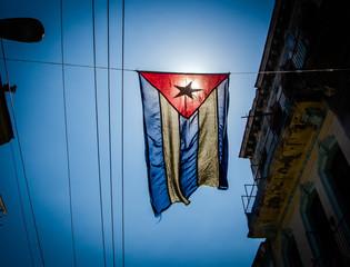 Cuban flag hangs in a street of the working-class neighborhood of Central Havana
