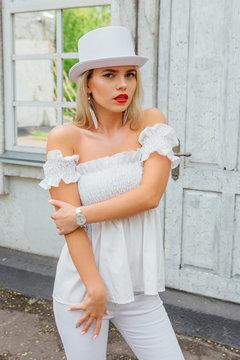 Sexy modern bride in white cylinder hat standing next to old vintage door and mirror window.