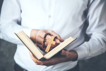 man hand cross with book on dark background