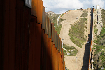Construction workers in the U.S. work on a new section of the border fence as seen from Tijuana