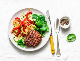Beef steak with grilled  vegetables, sweet pepper, zucchini and fresh spinach on a light background, top view. Delicious healthy balanced lunch