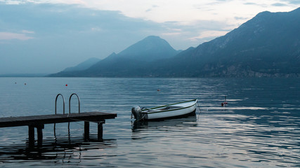 Beautiful landscape on lake Garda in Italy. Boat near the pier on the water surface of the water. The blue hues of the mountains.