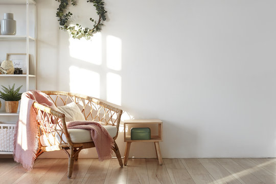 Scandinavian home interior with woven armchair on wooden floor, textile and decorative plants, evergreen wreath hanging on white wall with copy space for your inscription or mock up poster
