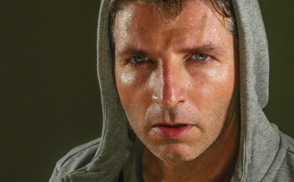 close up sweaty face portrait of young attractive and fierce looking man wearing hoodie posing in aggressive and defiant attitude isolated on dark background