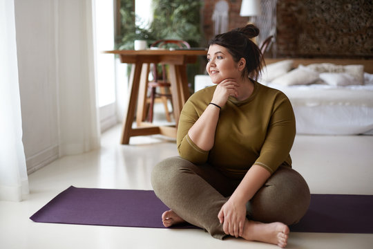 Young woman sitting on yoga mat