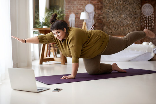 Woman doing yoga while looking at laptop