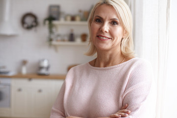 Indoor image of brown eyed middle aged Caucasian female in neat pink sweater posing against blurred kitchen interior background crossing arms on her chest and smiling joyfully. Maturity and age
