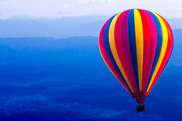 Colorful hot air balloon on blue mountain background