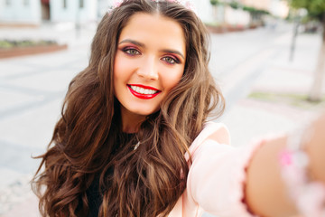 Beautiful brunette girl with perfect makeup, red lips and long wavy hair, holding camera in hand and taking self portrait. Fashionable and gorgeous woman making photo herself when walking at street.