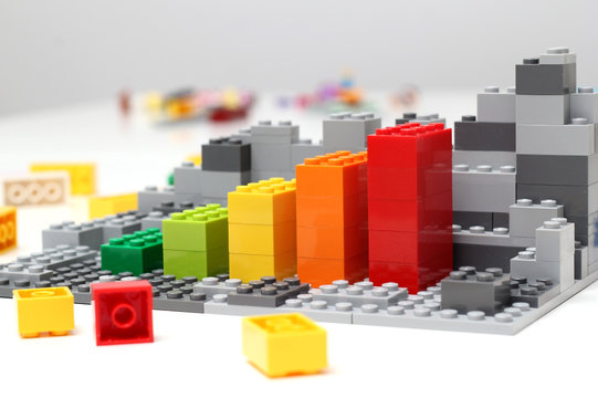 Progress chart made of bricks. Isometric composition of colourful toys on white table.