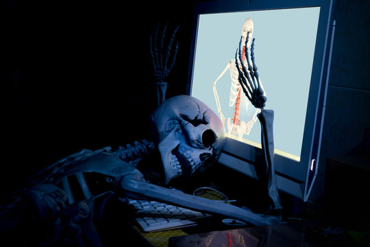 Fake human skeleton lying in front of desktop computer, computer addicted concept.