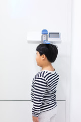 A fat boy is measuring his height himself in hospital