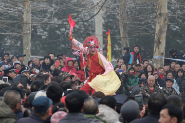 A performer on stilts dances during a folk art performance celebrating the Lantern Festival in Beijing