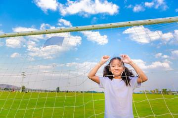 Little asian girl enjoy playing football on field