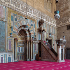 Colorful decorated marble wall with engraved Mihrab (niche) and wooden Minbar (Platform) at the Mosque and Madrassa (School) of Sultan Hassan, Cairo, Egypt