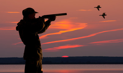 duck hunter at sunset background