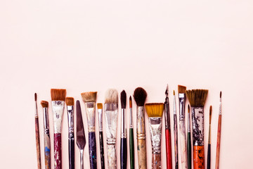 Row of different brushes. Art Creativity pink background